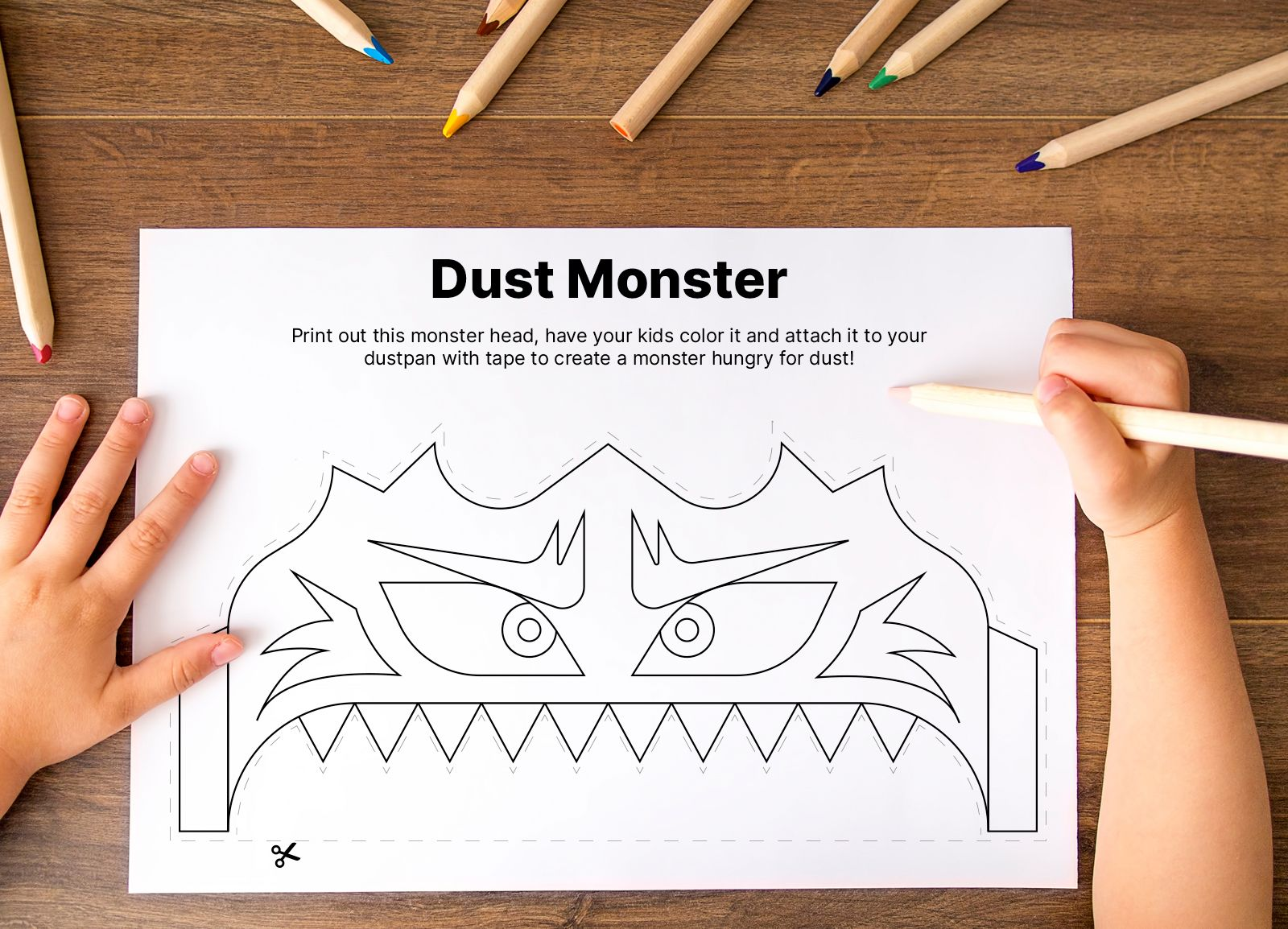 A child's hands prepare to color in a monster on a piece of paper.