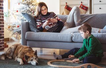 A boy playing with train tracks on a rug next to a dog, with a woman looking on her phone on a couch behind him
