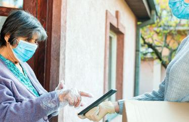 A woman in a mask delivering a package to a senior in a mask.