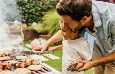 Man and his son grilling food
