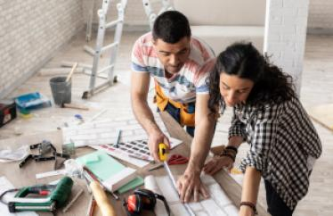 A man and a woman look over blueprint plans for a home. The man is measuring the plans with a tape measure. They are surrounded by tools.