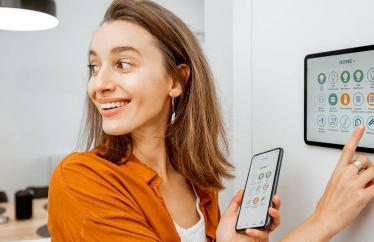 A woman smiling while using a tablet in the wall and holding a smart phone